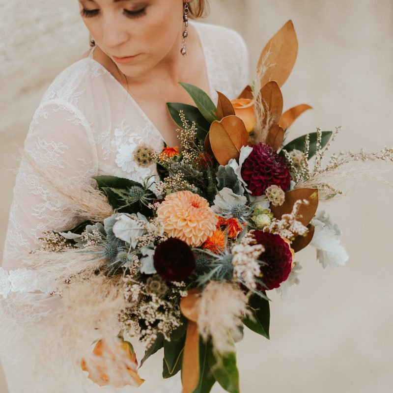 Bride in lace wedding dress holding large floral bouquet close to her