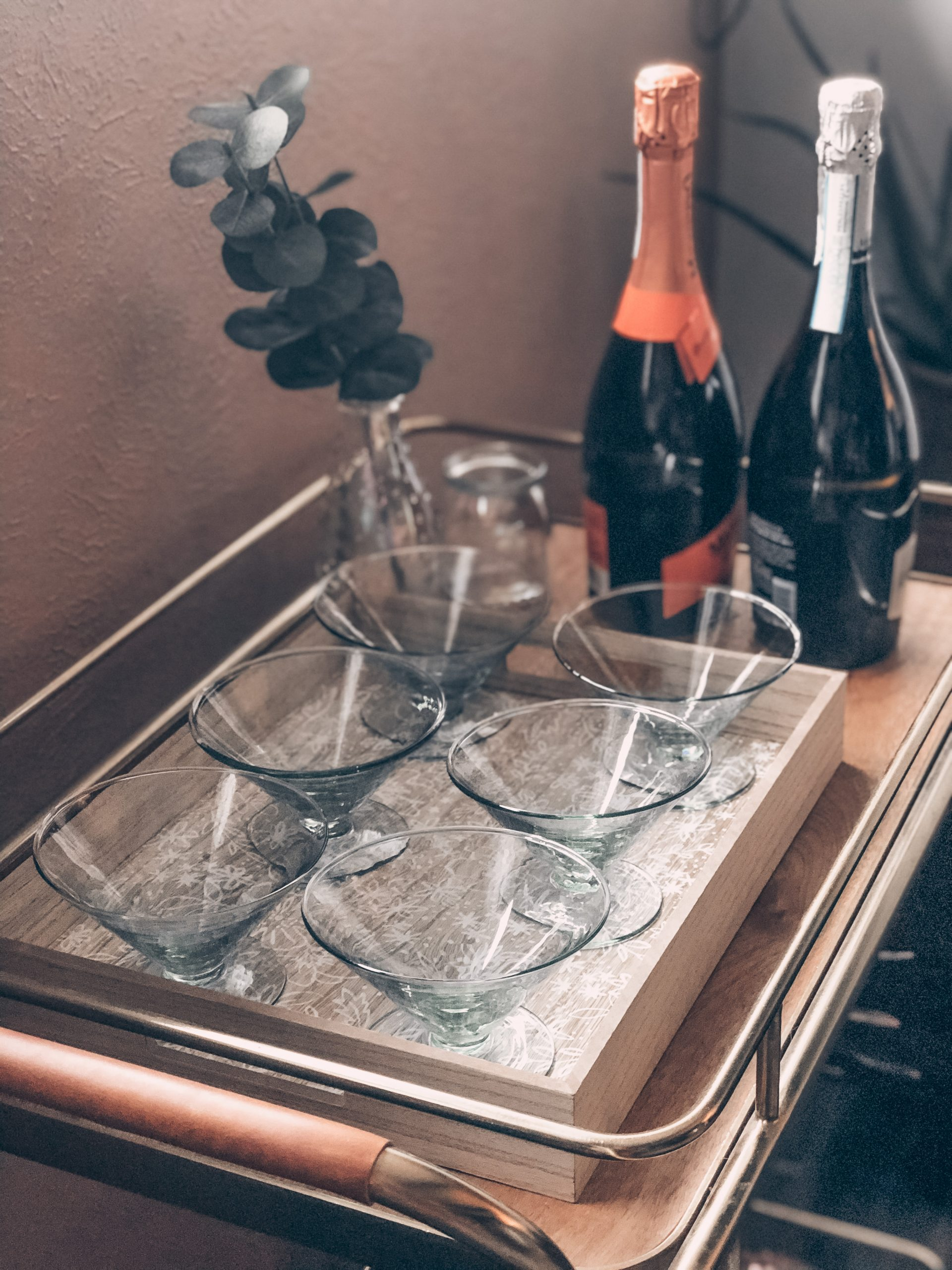 Drinking glasses and champagne on beverage cart