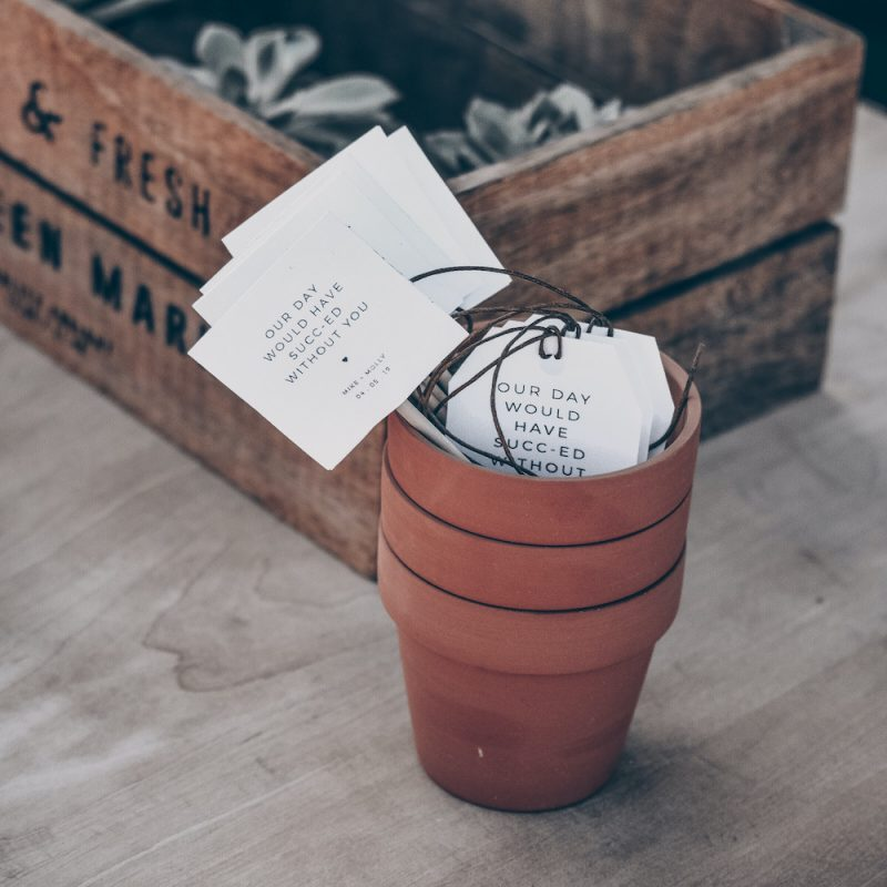 """Terracotta pot filled with tags that say """"Our day would have sucked without you."""""""