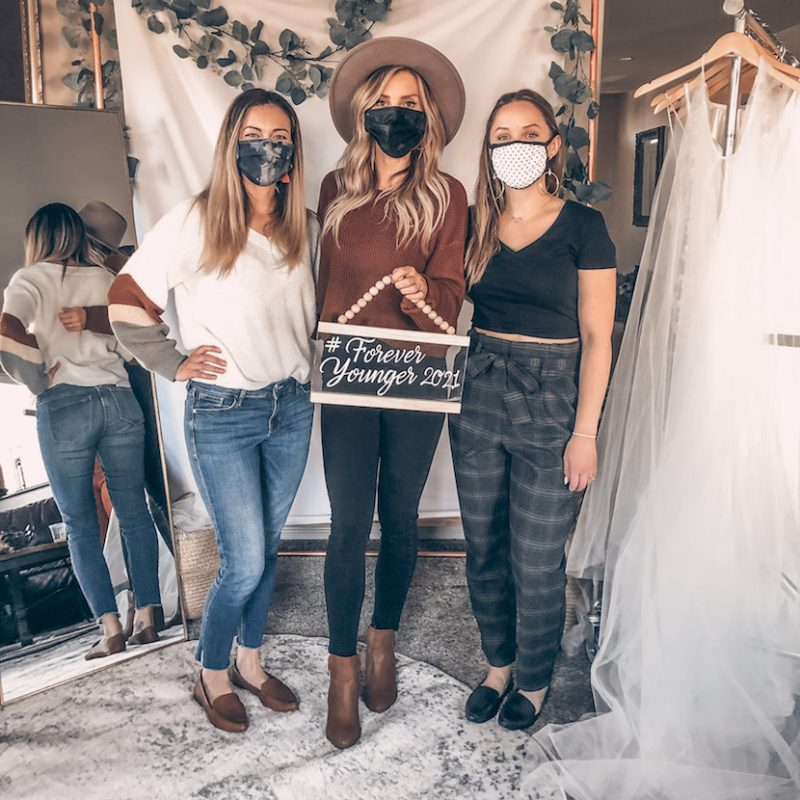 Three women at a bridal appointment wearing masks and standing near dresses