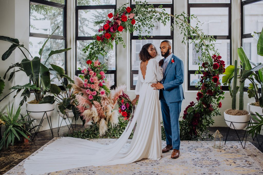 A bride and groom in front of a floral arch indoors with a rug and natural light