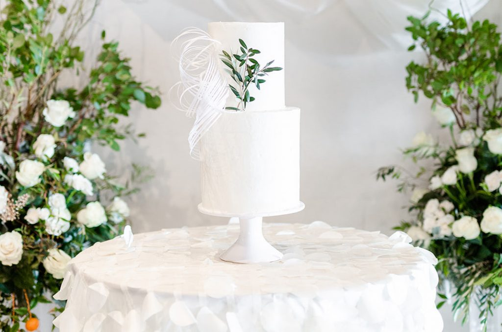 White tiered wedding cake on white round table with greenery