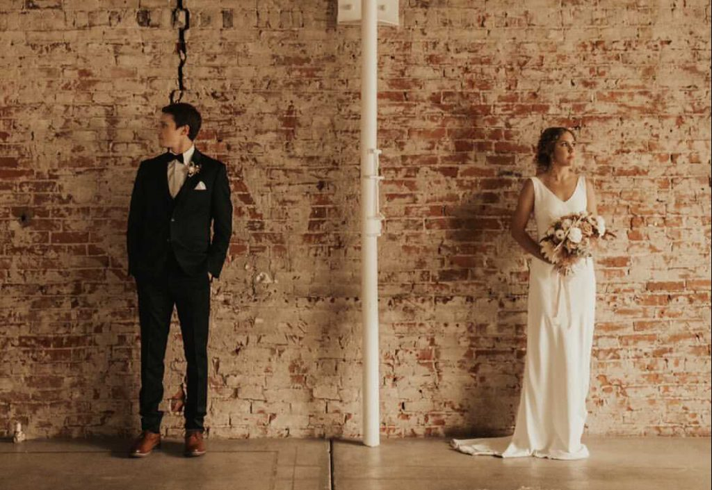 Husband and wife man and woman in front of brick wall modern wedding