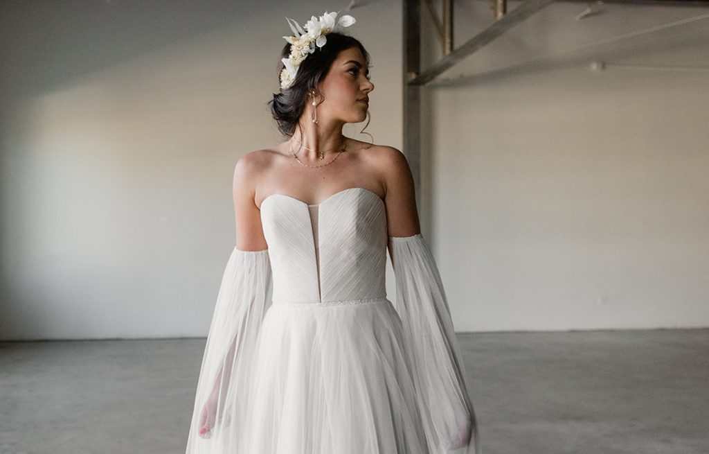 Woman with bridal updo and floral crown in tulle wedding dress with sleeves