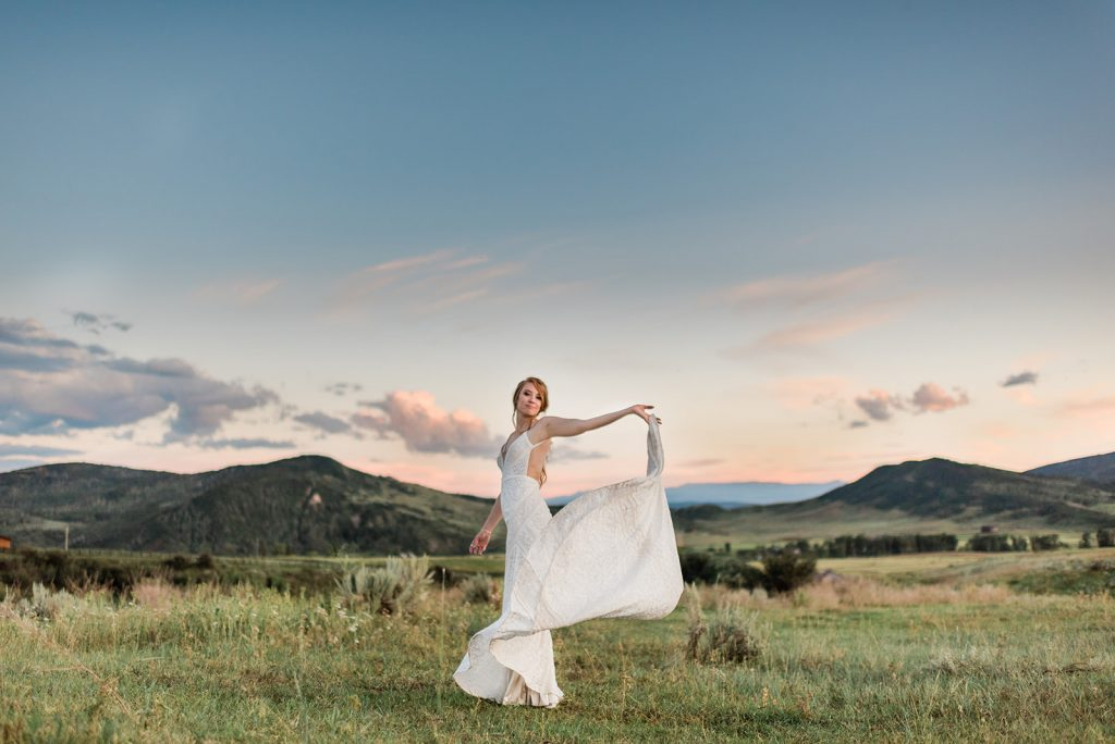 Woman in field by Colorado Rocky Mountains in White Wedding Dress Dancing