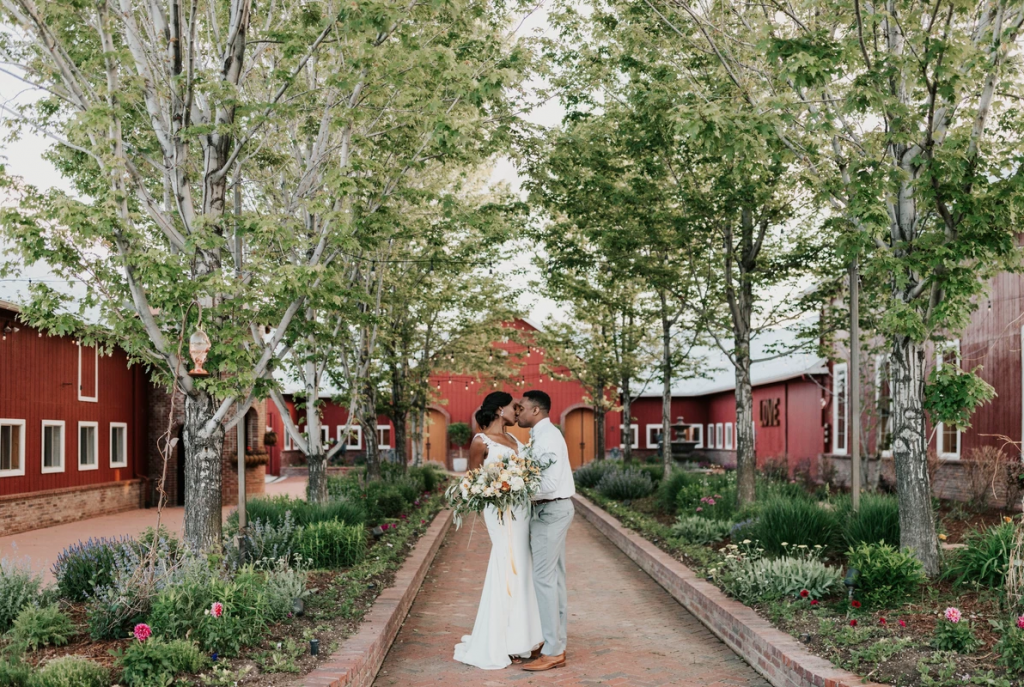 Man and woman becoming husband and wife in front of red barn with trees and floral