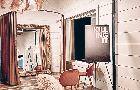 A room with a mirror and chairs and white walls