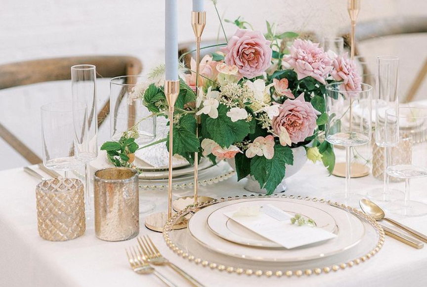 A table scape with white background gold cutlery and floral