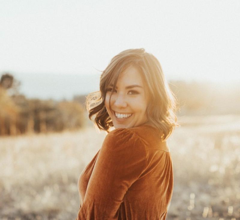Woman in orange dress in a field sunlight fall