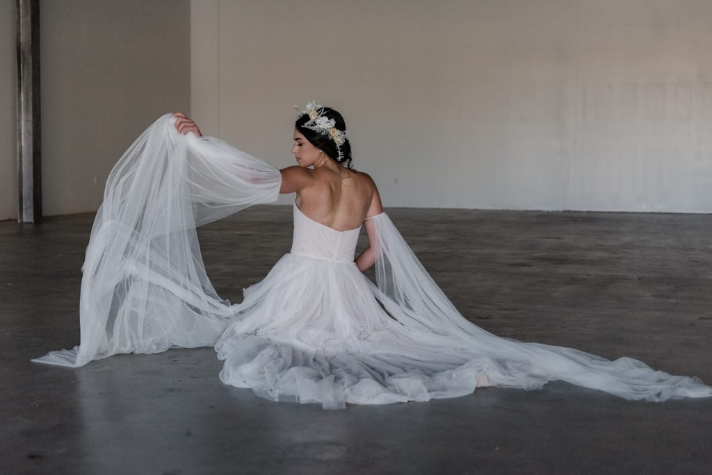 A woman in a flowing wedding dress on a concrete floor