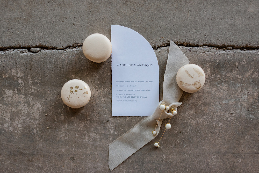 French macarons on a concrete ground next to jewelry and an invitation