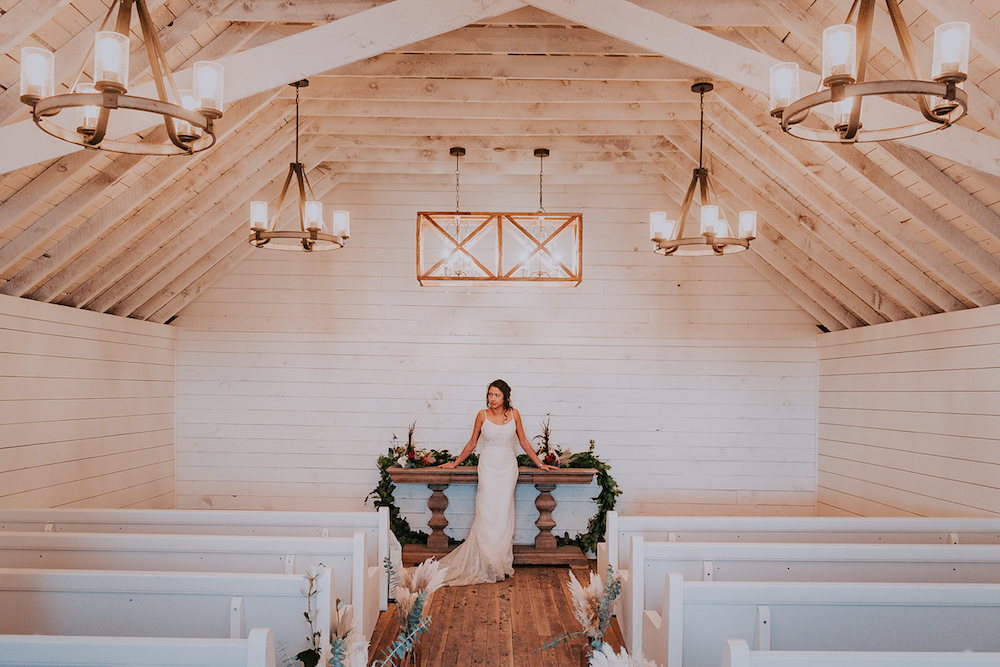 A woman in a church in a wedding dress with floral