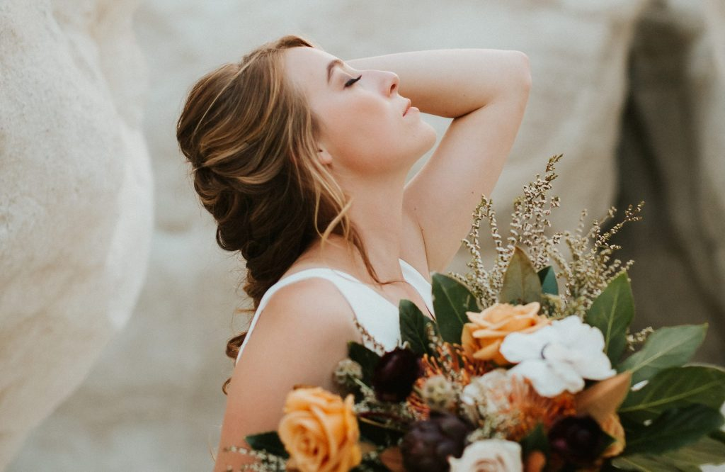 Woman with braided wedding hair in white dress and floral bouquet