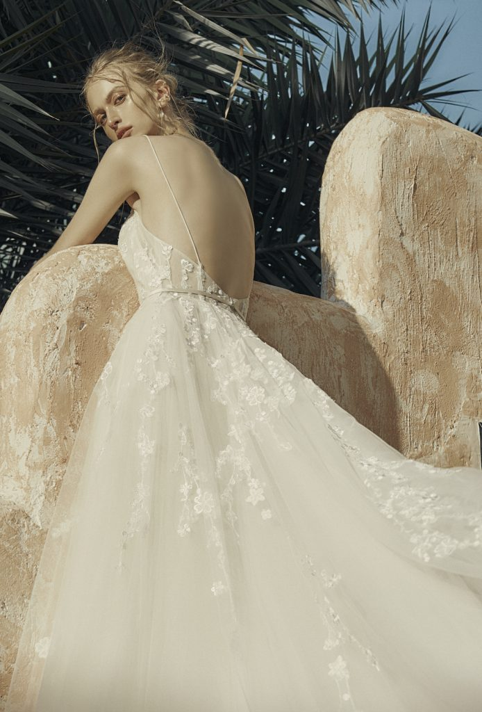 Woman in thin strapped wedding dress with full tulle skirt looking back at camera
