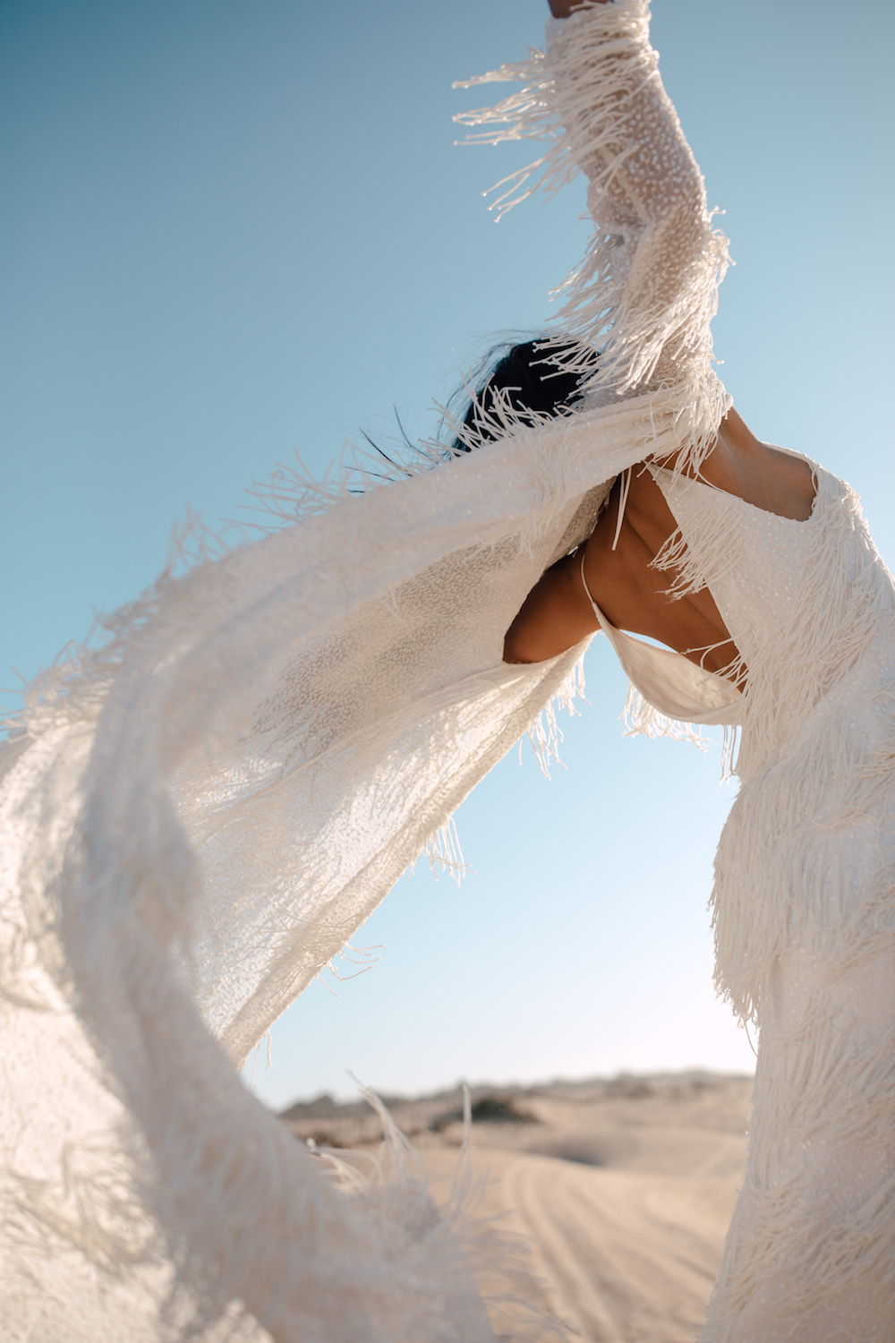 women in wedding dress with fringe overdress on beach