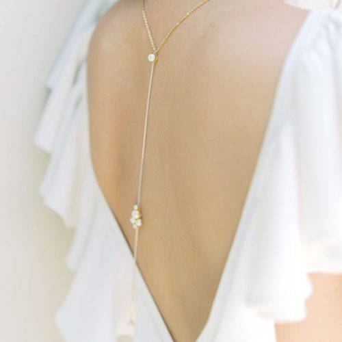 A Gold Back Chain with an Open Back White Dress