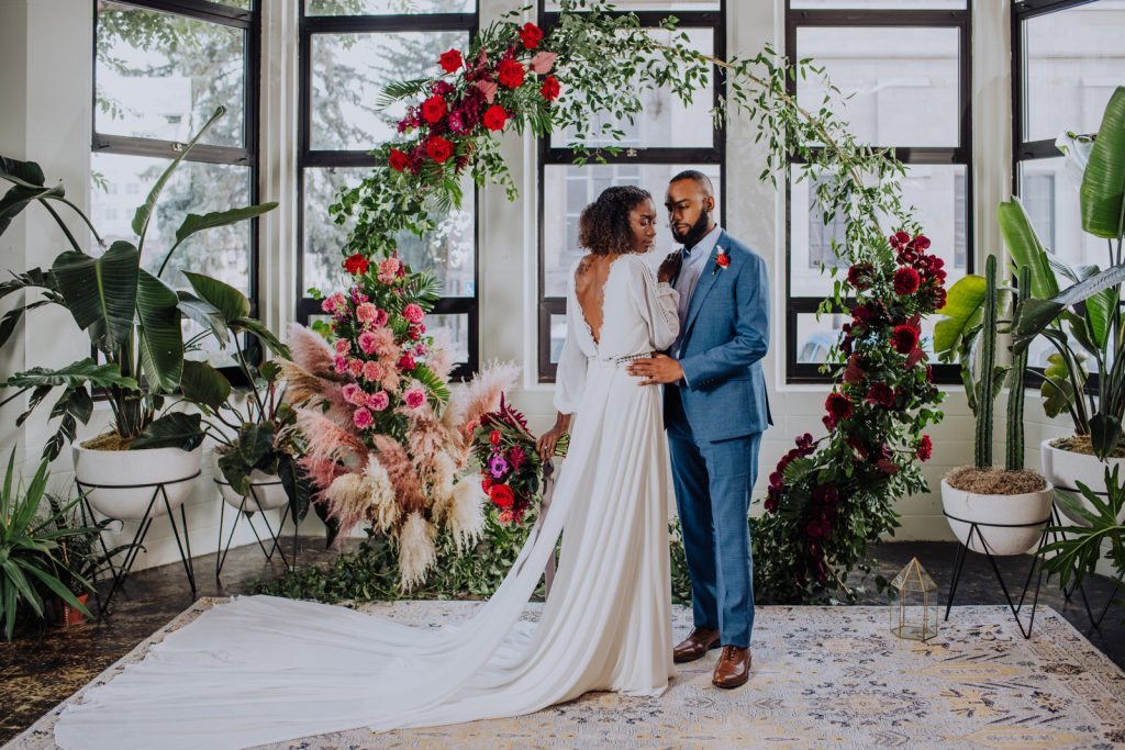 Bride in long sleeve wedding drss and groom in blue suit posing in front of a large floral wreath