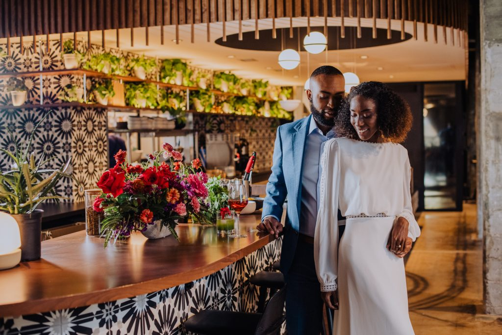 Bride and groom posing in front of a bar with cocktails next to them