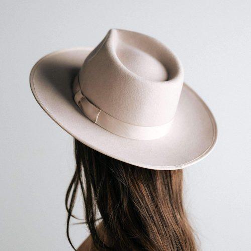 Woman modeling wide brim ivory hat