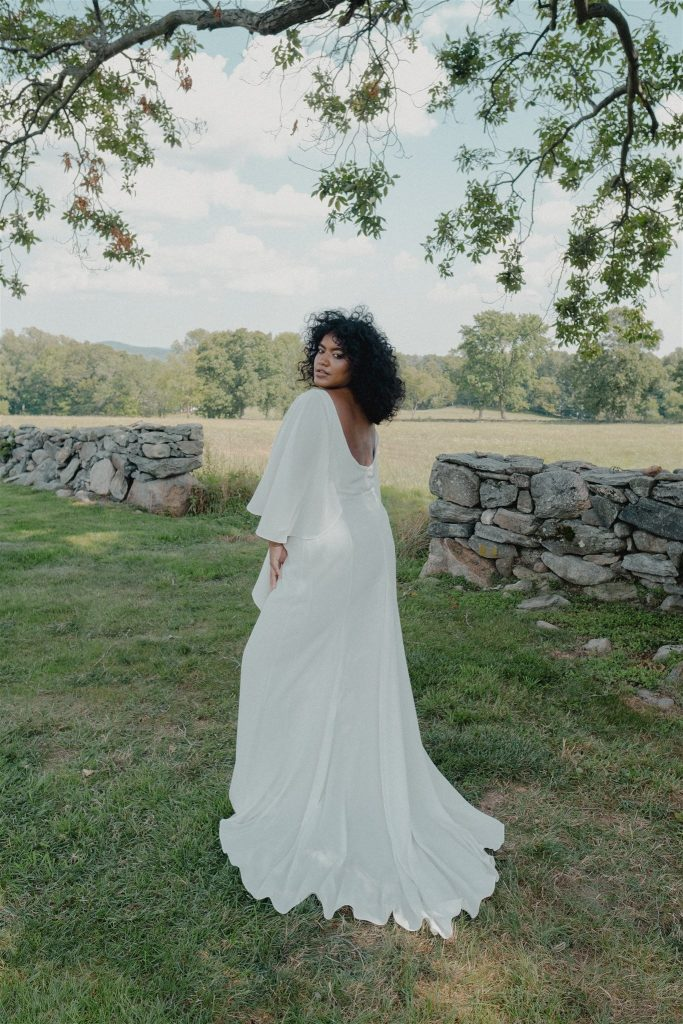 Woman standing in a field under a tree in a white wedding dress