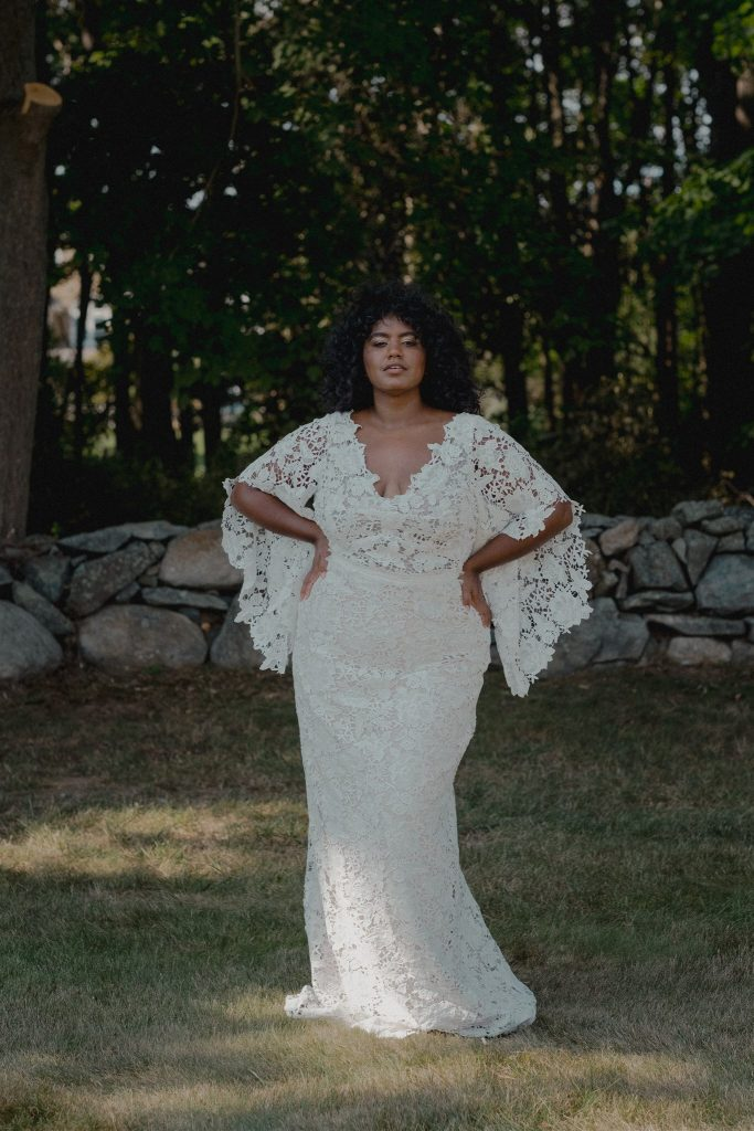 Woman modeling a white lace wedding dress with long flowing sleeves