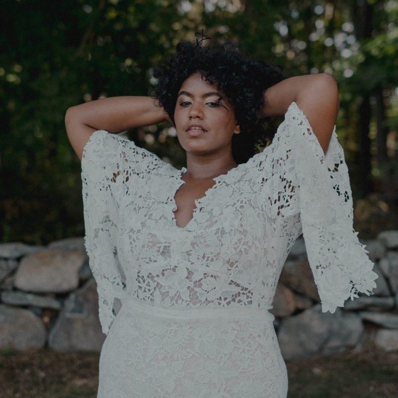 Woman posing in lace wedding dress.