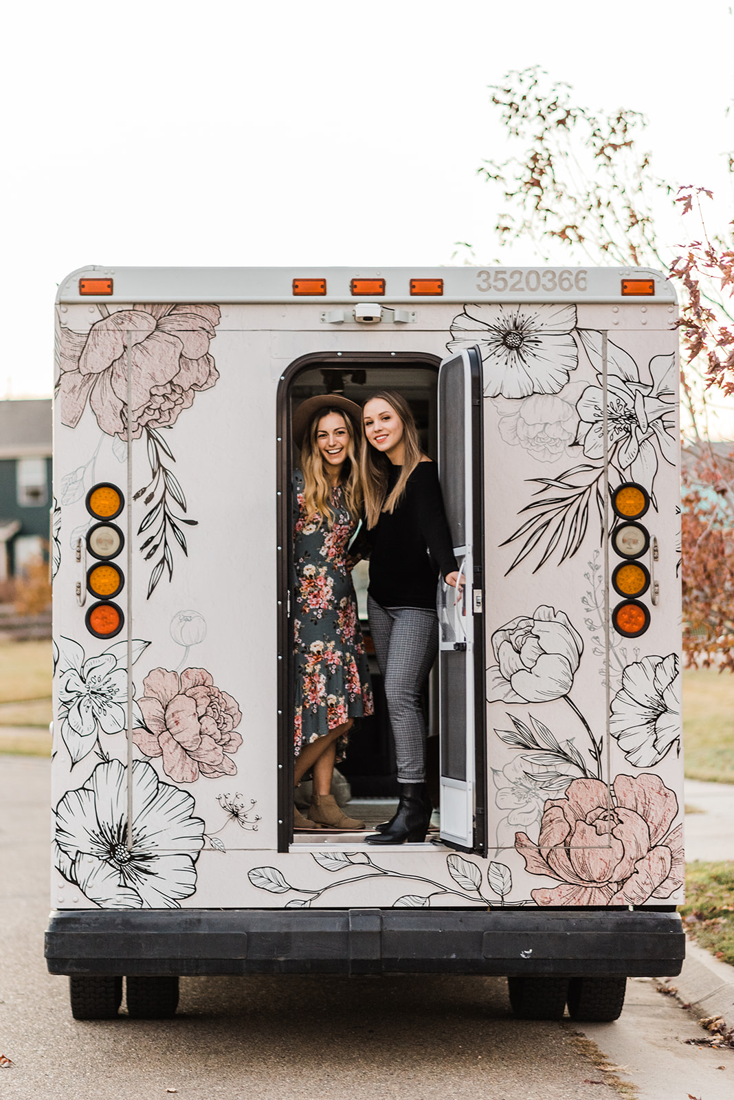 Two women in the back of a boutique floral wedding truck