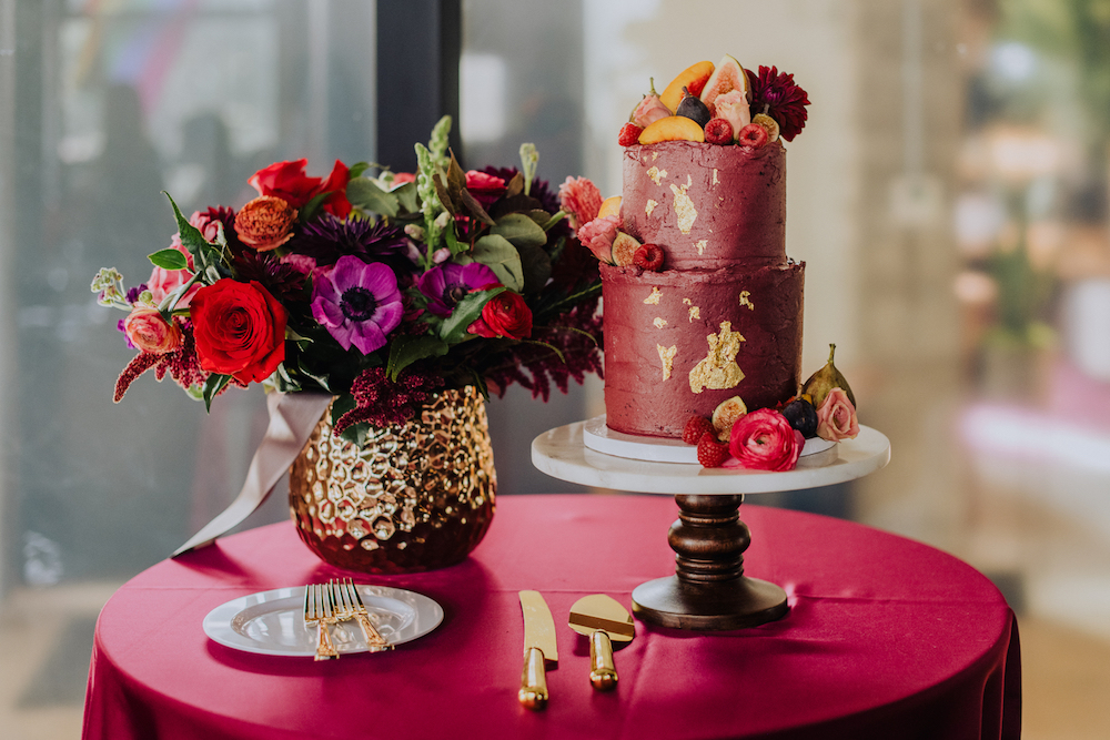 A jewel tone red cake with floral in a gold vase and gold cutlery