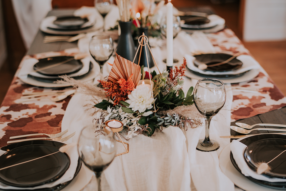 Tablescape with black plates and glassware, with floral and candles