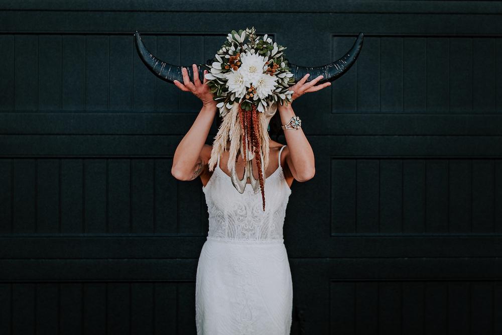 Woman in white wedding dress with floral bull head western wedding