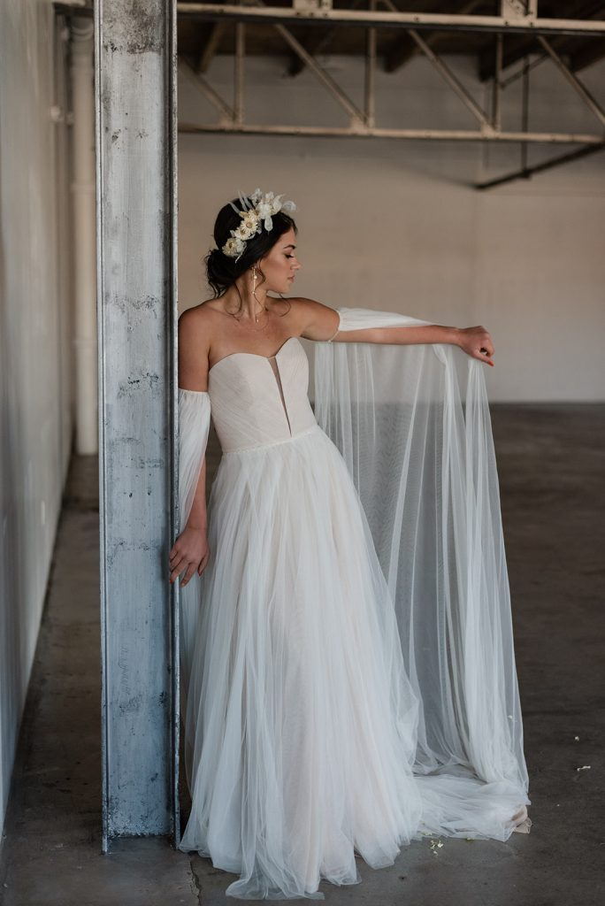 Bride leaning against metal post in tulle wedding dress with long sleeves