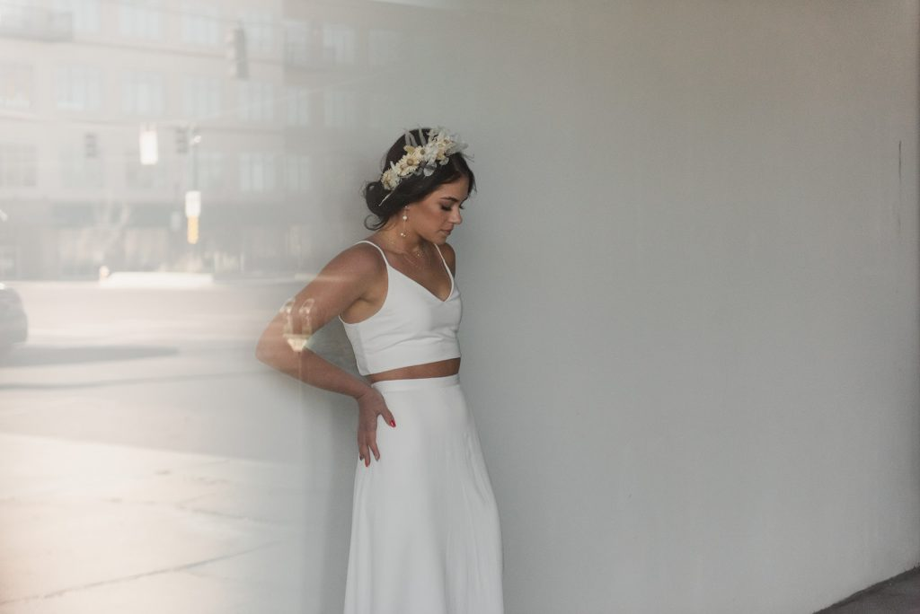 Bride pictured through a window, looking at the ground