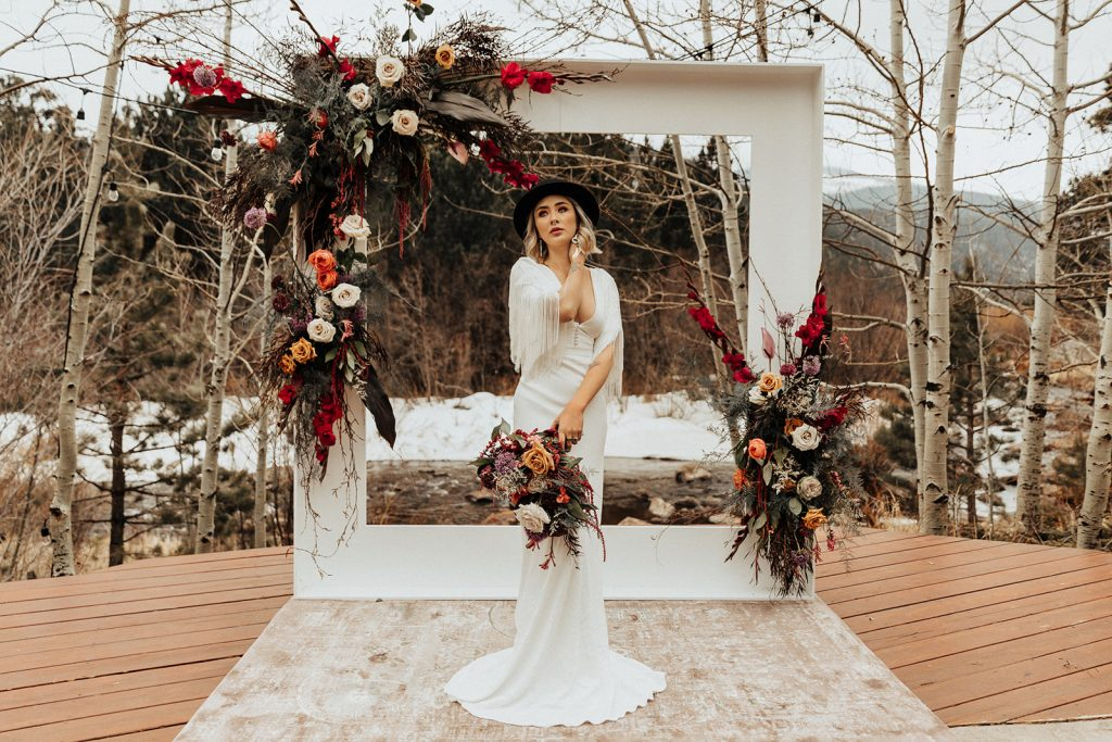 A boho bride outside in front of a floral arch