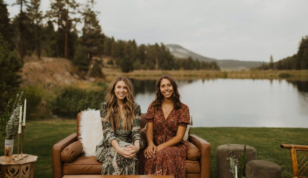 Two women on a couch outside in front of a lake