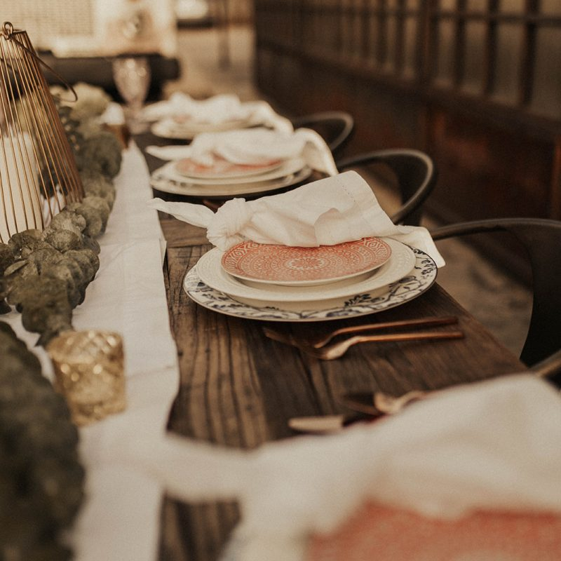 Rustic table setting with pink salad plates and white napkins on a wooden table