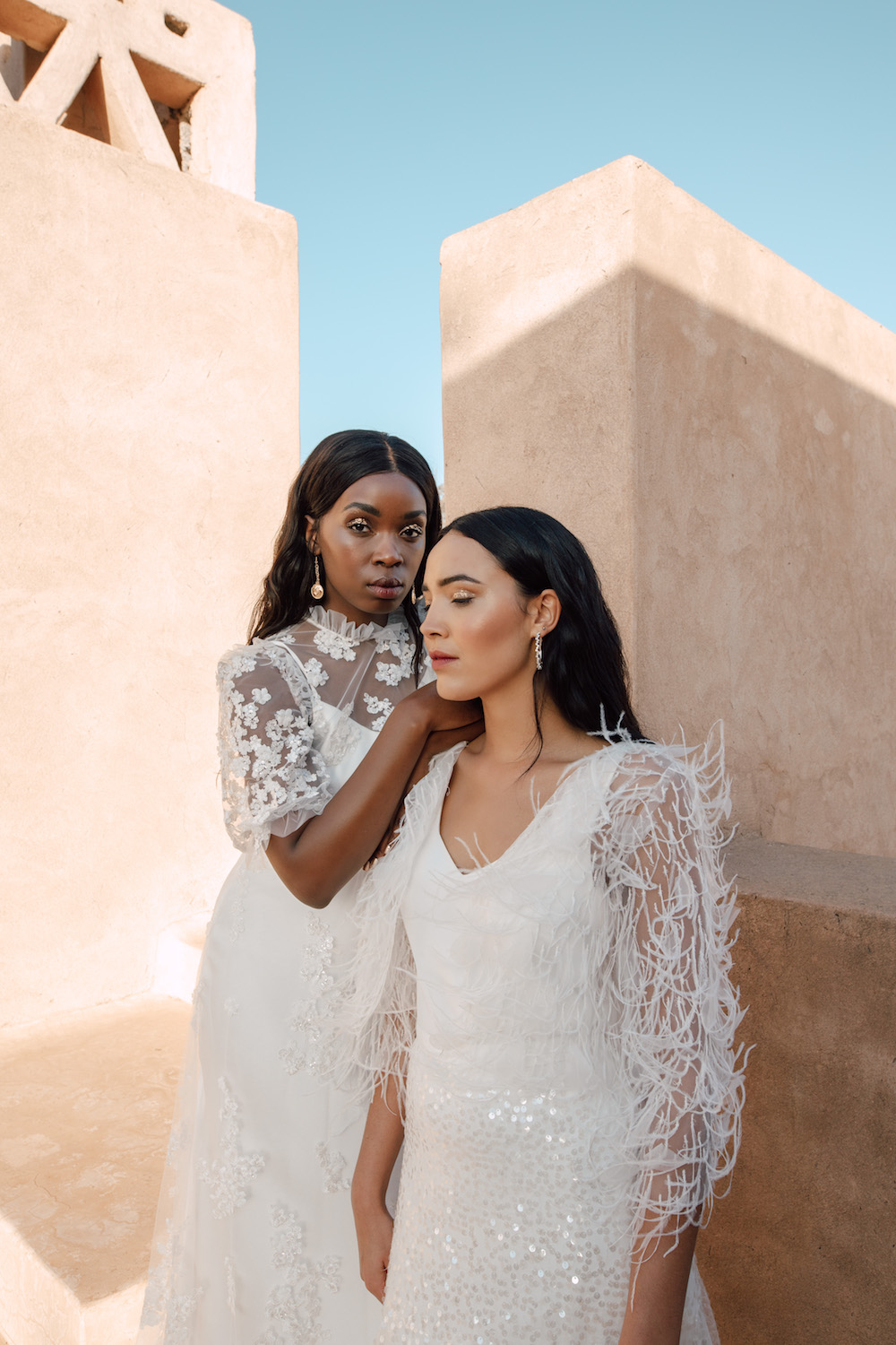 Two women in wedding dresses outside next to terra cotta building