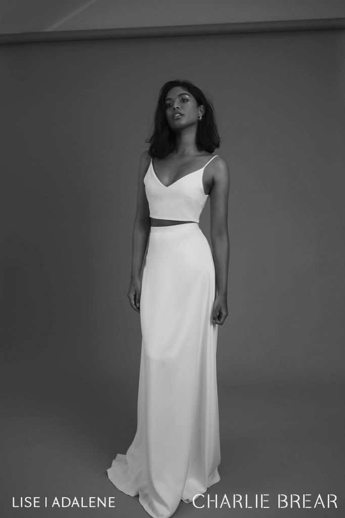 Woman posing in two piece white wedding dress with black background