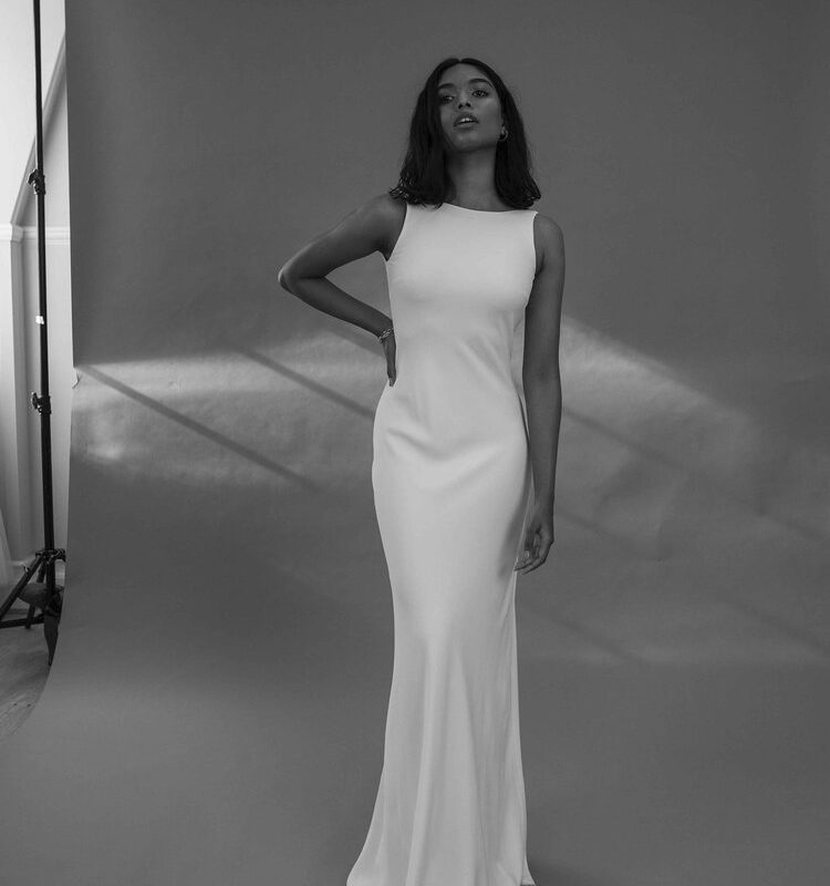 Model in high neck white wedding dress with black background