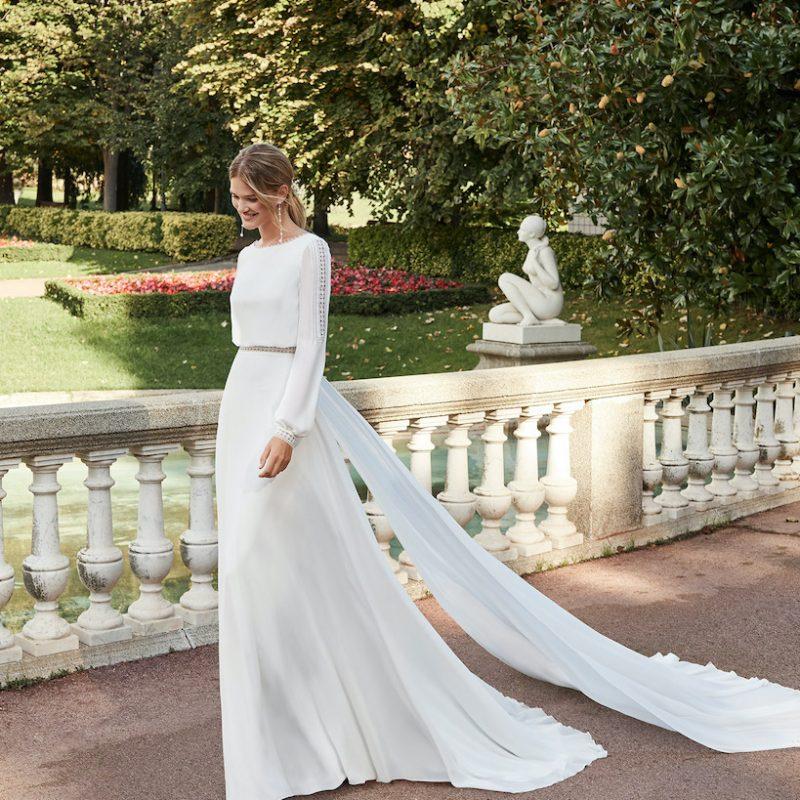 Woman walking in long sleeved white bohemian wedding dress
