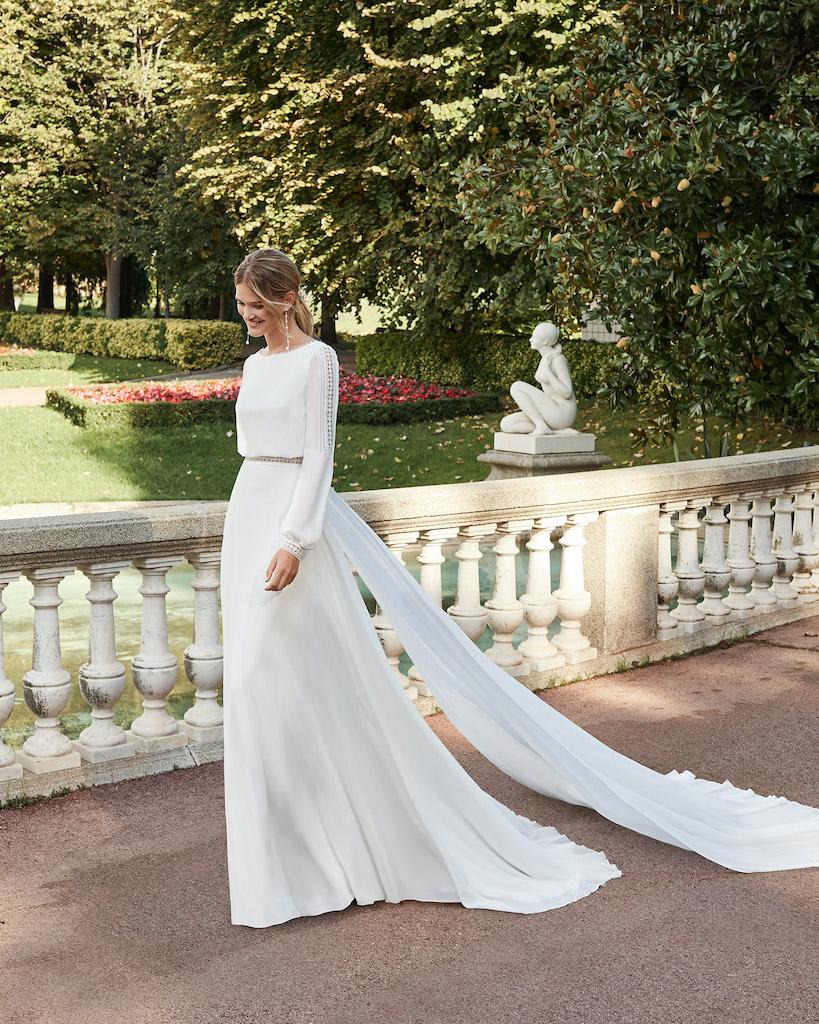 Woman walking in long sleeved white bohemian wedding dress by Aire Barcelona