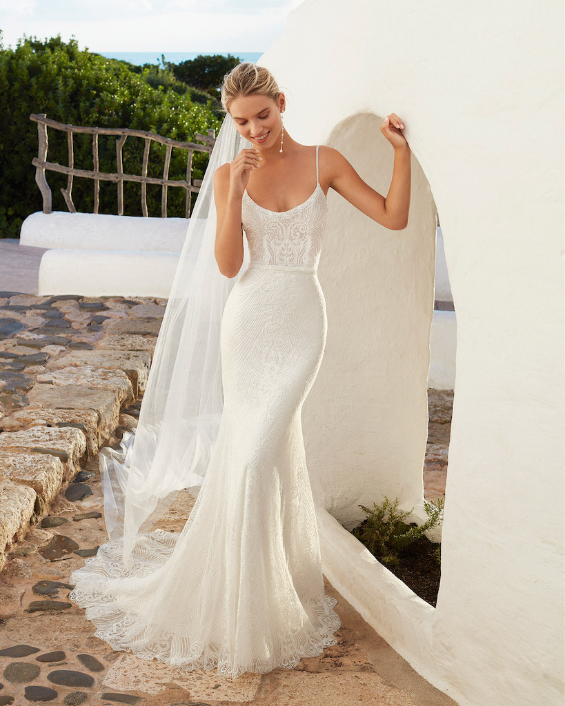 woman leaning against wall in Aire Barcelona fit and flare wedding dress
