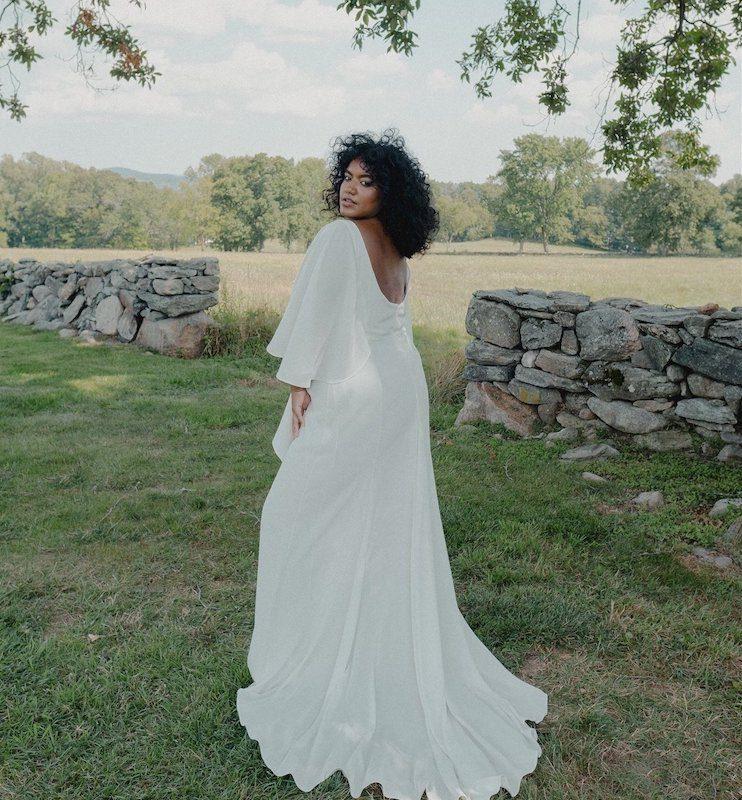 Bride posing in flowing wedding dress in middle of field