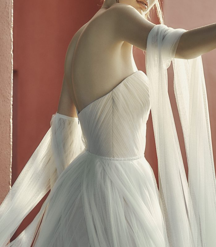 Woman posing in flowing tulle wedding dress against red wall