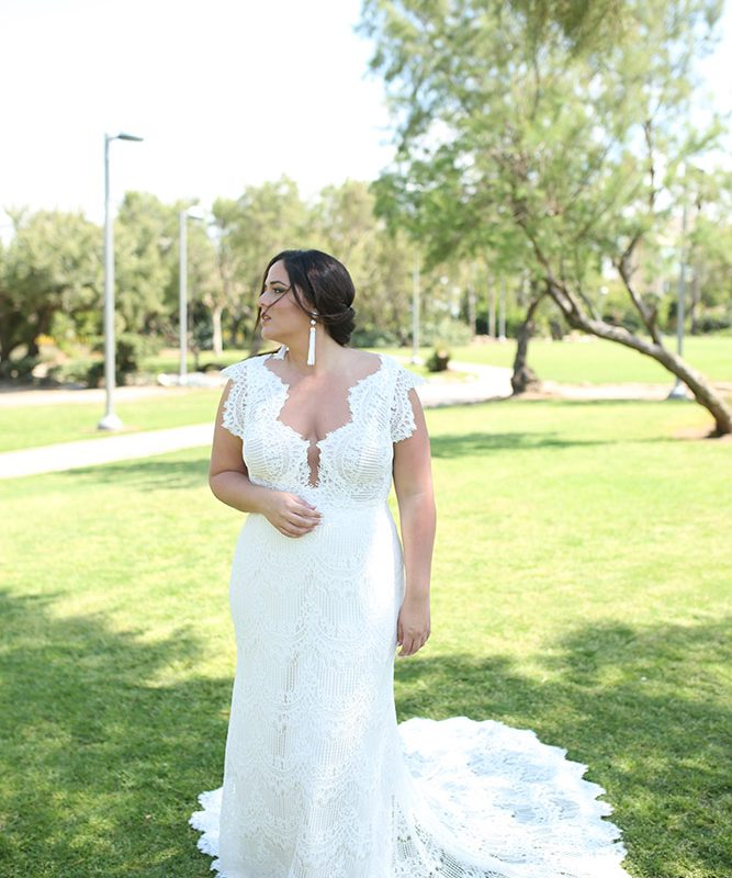 Women standing in grass in white lace wedding dress