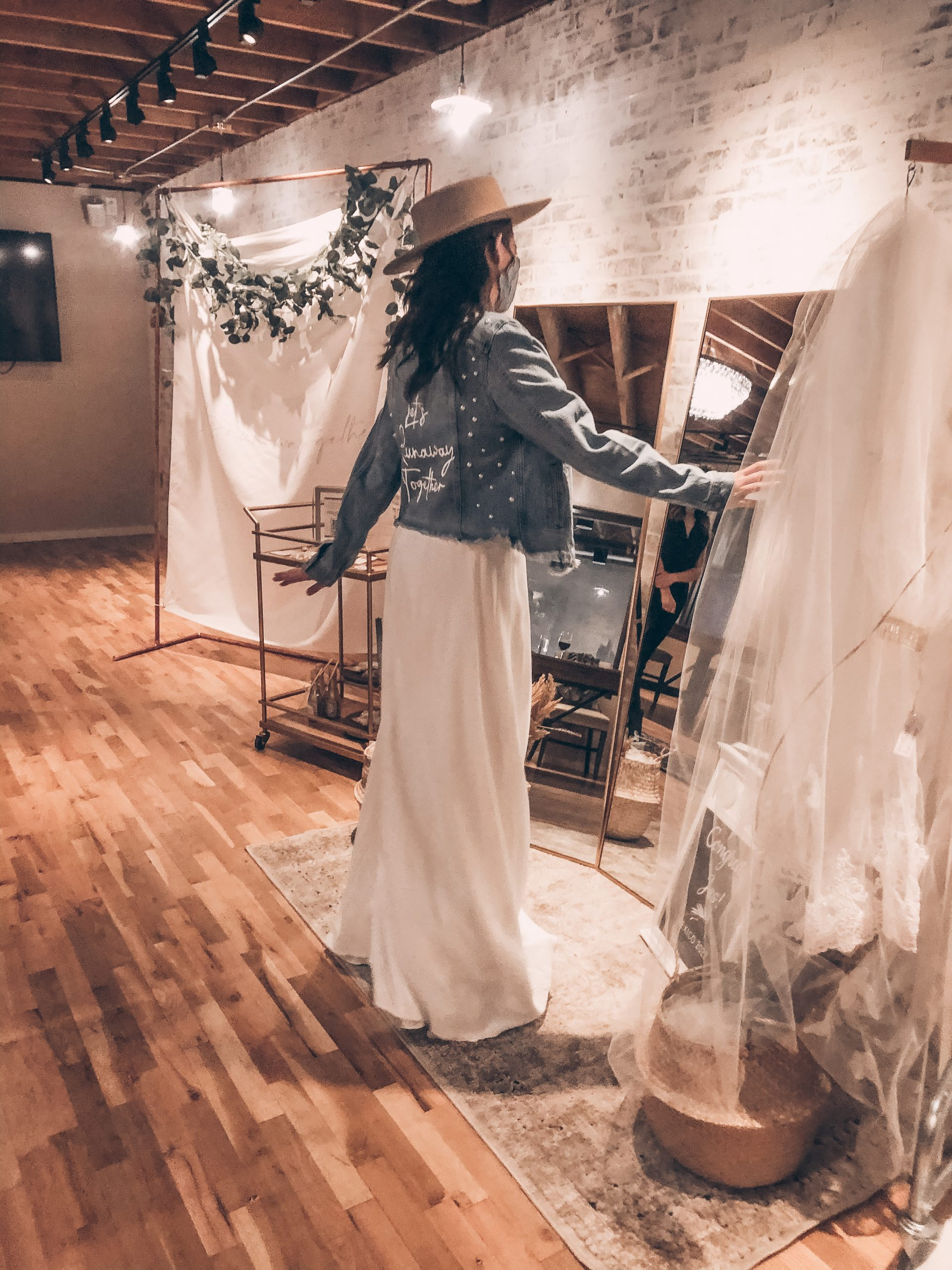 A bride in a denim jacket looking at her wedding dress in mirrors