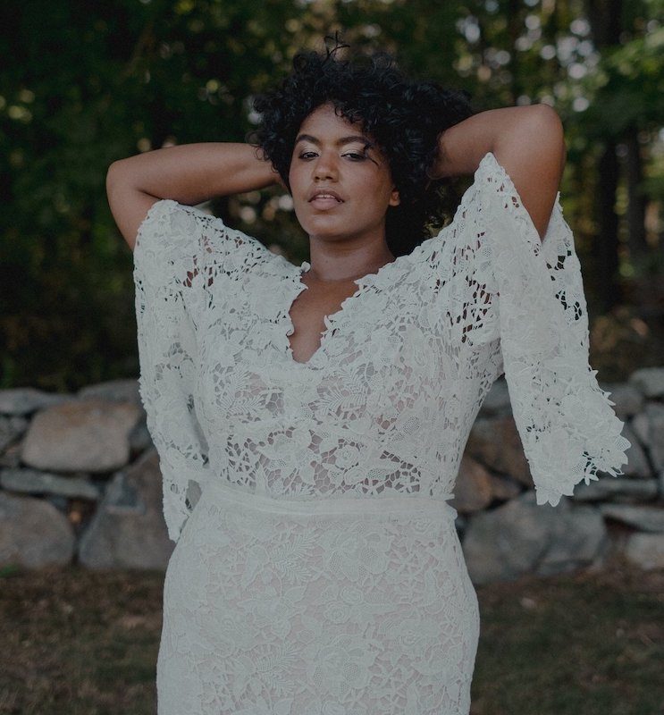 Woman with hands behind head posing in white lace wedding dress