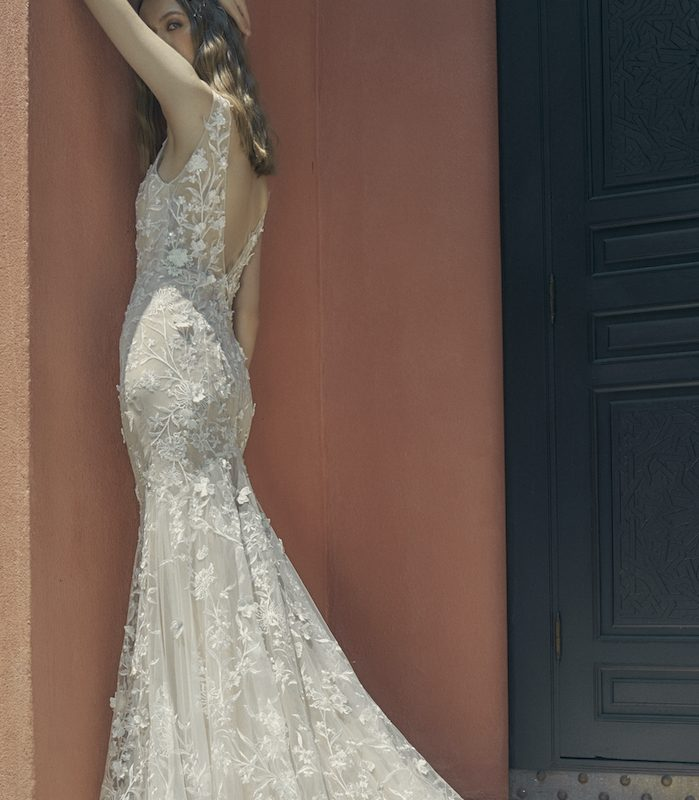 Woman standing against red wall in off white wedding dress