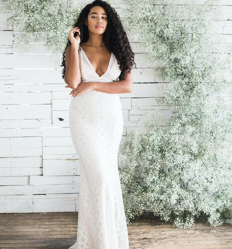 Bride posing in lace wedding dress in front of floral arch