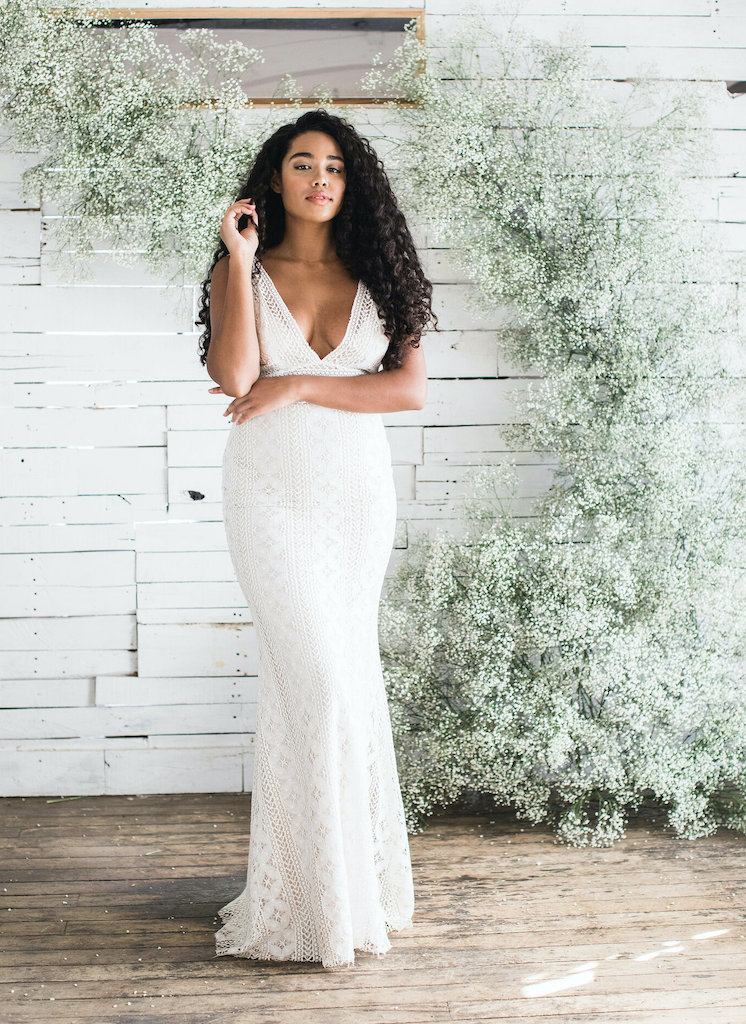 Bride posing in Loulette lace wedding dress in front of floral arch