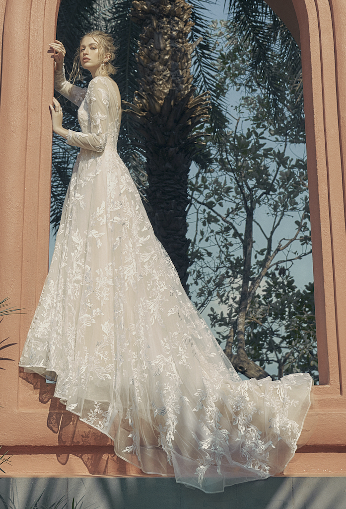Woman posing in blush colored long sleeve wedding dress by red building